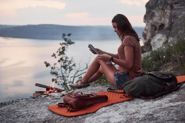 Junges mädchen des hipsters mit rucksack, der sonnenuntergang auf spitze des felsenberges genießt. touristenreisender auf hintergrundansichtsmodell