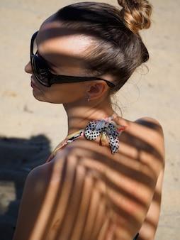 Junges mädchen des porträts in der sonnenbrille auf dem strandschatten durch palmenniederlassung.