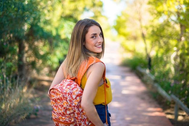 Junges mädchen des studenten mit rucksack in einem park
