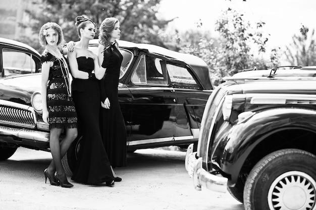 Junges mädchen drei im retrostilkleid nahe alten klassischen weinleseautos.