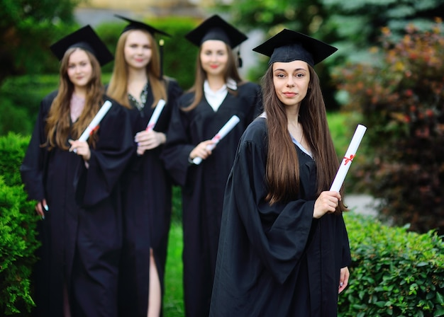 Junges mädchen, ein hochschulabsolvent in einem schwarzen gewand und einem quadratischen hut mit einem diplom in den händen, lächelt vor dem hintergrund der klassenkameraden der studenten.