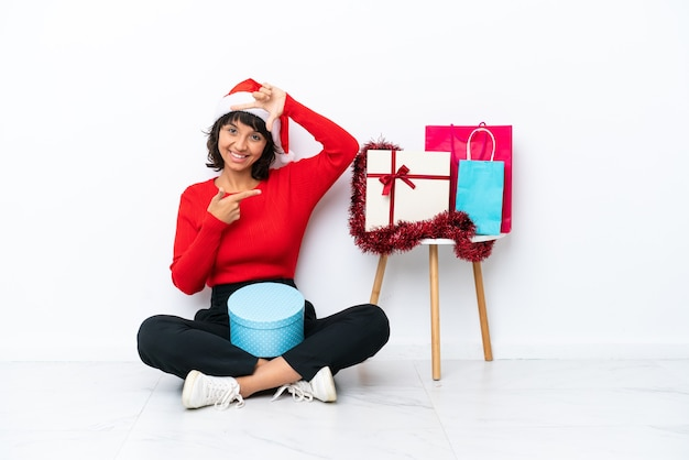 Junges mädchen feiert weihnachten auf dem boden sitzend isoliert auf weißem bakcground fokussierung gesicht. rahmensymbol