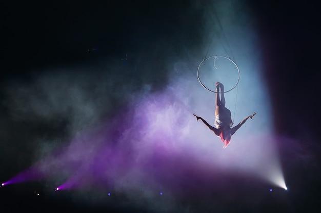 Junges mädchen führt die akrobatischen elemente im luftring aus