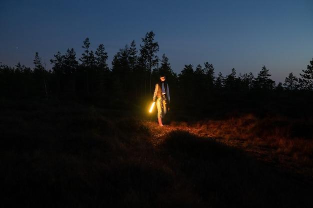 Junges mädchen geht nachts durch die landschaft und hält eine led-lampe, um den weg zum lager oder zum auto nach dem wandern hervorzuheben