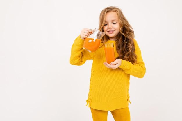 Junges mädchen gießt karottensaft aus einem krug in ein glas
