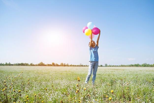 Junges mädchen hält bunte luftballons am blumengras mit blauem himmel