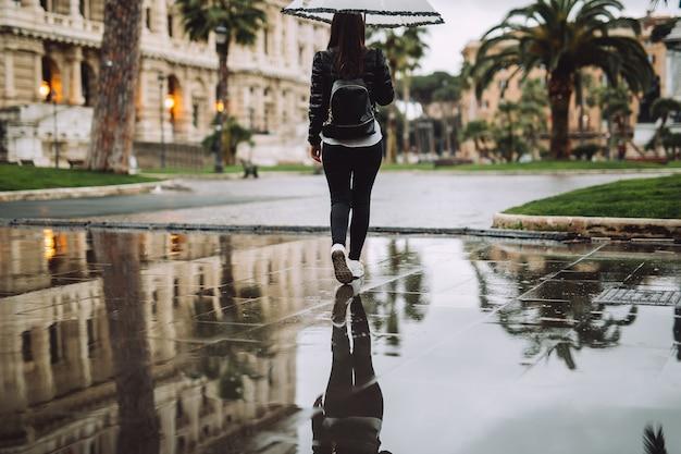 Junges mädchen hält den regenschirm, sie reflektiert im wasser