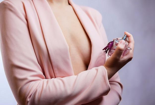 Junges mädchen hält ein parfümglas in der hand, rosa mantel, halbnackte brust