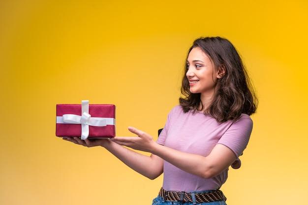 Junges mädchen hält eine geschenkbox an ihrem jahrestag und sieht glücklich aus