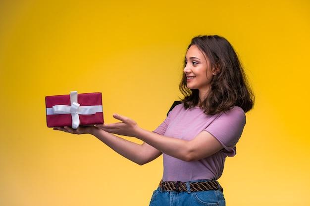 Junges mädchen hält eine geschenkbox an ihrem jahrestag und sieht glücklich aus.