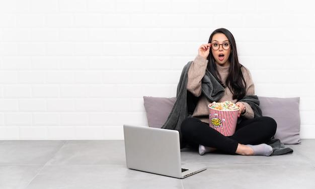 Junges mädchen hält eine schüssel popcorn und zeigt einen film in einem laptop mit brille und überrascht