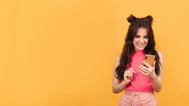 Junges mädchen hält ihr smartphone in den händen und schaut lächelnd auf den bildschirm auf orangem hintergrund