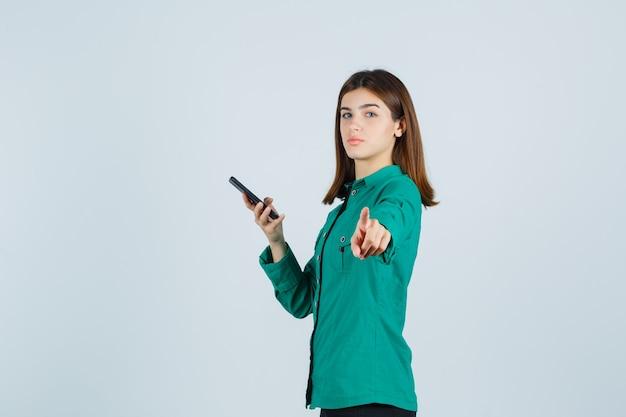 Junges mädchen hält telefon in einer hand, zeigt auf kamera in grüner bluse, schwarze hose und sieht ernst aus. vorderansicht.