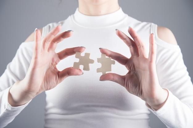 Junges mädchen hält zwei puzzleteile