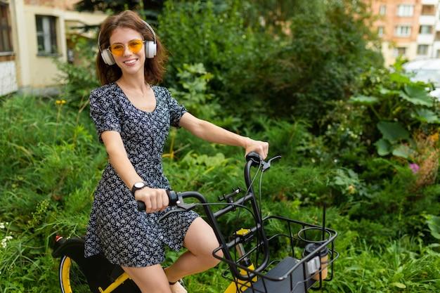 Junges mädchen hören musik und fahren fahrrad im park mit einer guten stimmung