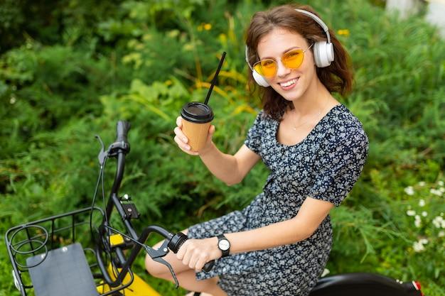 Junges mädchen hören musik und fahren fahrrad im park mit einer tasse kaffee