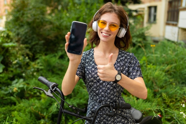 Junges mädchen hören musik und fahren fahrrad mit ihrem telefon im park