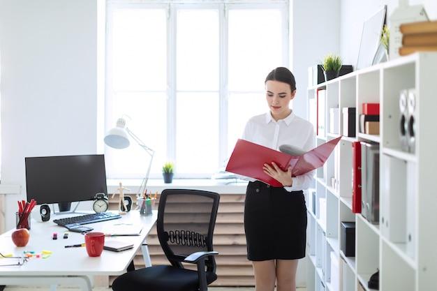 Junges mädchen im büro nahe dem gestell und blättern durch den ordner mit den dokumenten.