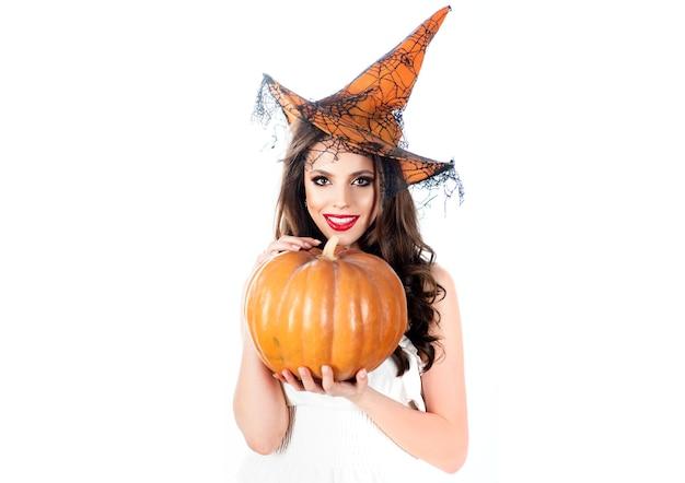 Junges mädchen im halloween-kostüm. geheimnisse der magie. frauenhexe mit kürbis. halloween-schönheits-hexe. süßes oder saures. feier herbstferien halloween.
