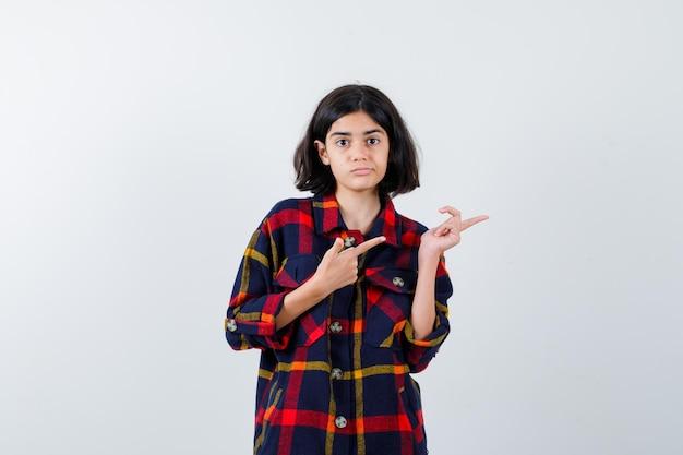 Junges mädchen im karierten hemd, das mit den zeigefingern nach rechts zeigt und hübsch aussieht, vorderansicht.