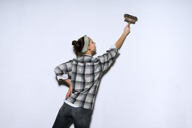 Junges mädchen im karierten hemd färbt die wände weiß, reparatur