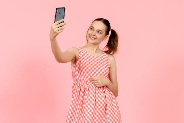 Junges mädchen im niedlichen hellen kleid, das selfie auf rosa nimmt