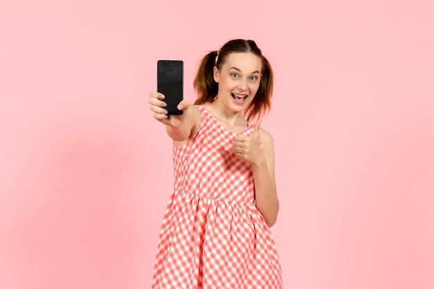 Junges mädchen im niedlichen hellen kleid, das telefon auf rosa hält