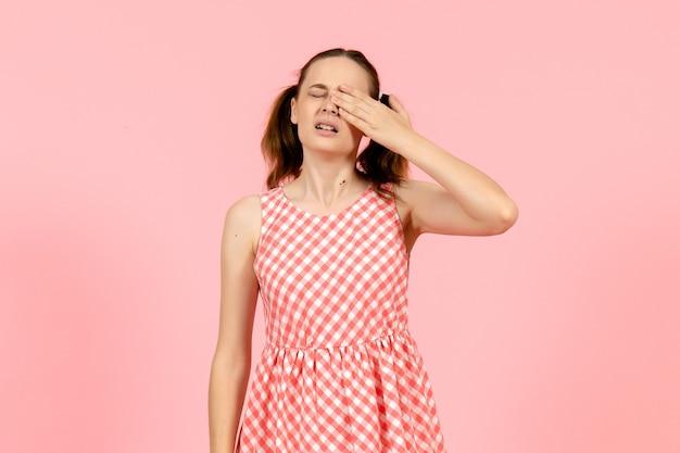 Junges mädchen im niedlichen rosa kleid, das auf rosa weint