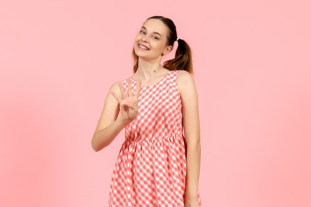Junges mädchen im niedlichen rosa kleid, das nummer auf rosa zeigt