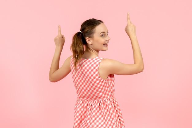 Junges mädchen im niedlichen rosa kleid mit aufgeregtem ausdruck und wieder auf rosa gedreht