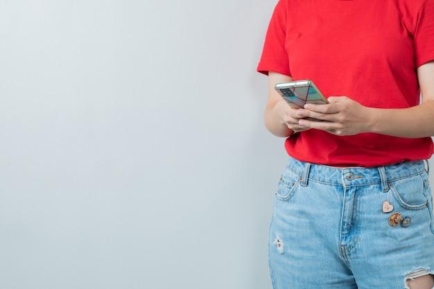 Junges mädchen im roten hemd, das ein silbernes smartphone hält