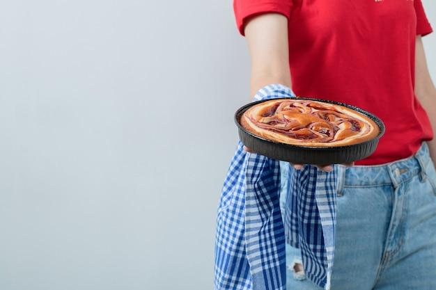 Junges mädchen im roten hemd, das einen kuchen in einer schwarzen pfanne hält
