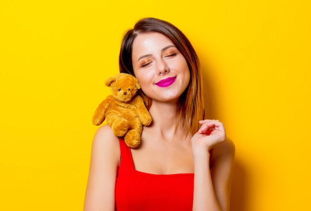Junges mädchen im roten kleid mit teddybärspielzeug auf ihrer schulter gelb