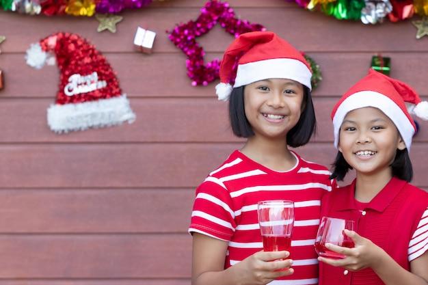Junges mädchen im roten kleid zeigt ein lächelngesicht und einen roten saft am weihnachtstag trinkend.