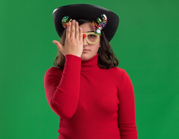 Junges mädchen im roten pullover, der lustige brille und schwarzen hut trägt, der ein auge mit hand bedeckt