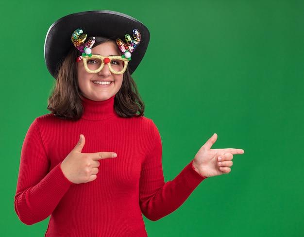 Junges mädchen im roten pullover trägt lustige brille und schwarzen hut, der kamera lächelnd betrachtet