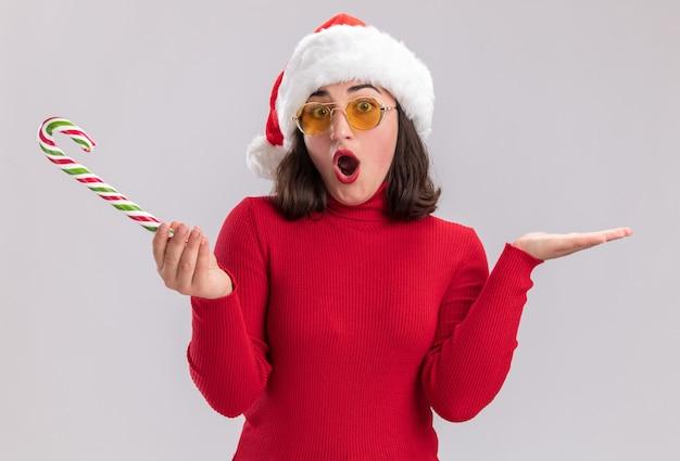 Junges mädchen im roten pullover und in der weihnachtsmannmütze, die brillen hält, die zuckerstange betrachten kamera betrachten, überrascht und verwirrt mit armen, die über weißem hintergrund stehen
