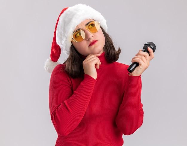 Junges mädchen im roten pullover und in der weihnachtsmannmütze, die die brille hält, die mikrofon hält, das verwirrt über weißem hintergrund steht