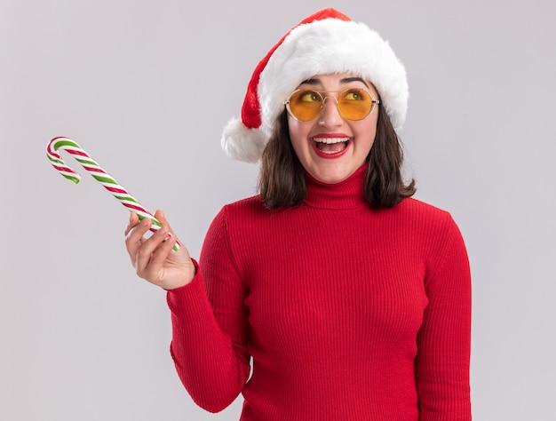 Junges mädchen im roten pullover und in der weihnachtsmannmütze, die die brille hält, die zuckerstange hält, die beiseite mit glücklichem gesicht steht, das über weißem hintergrund steht