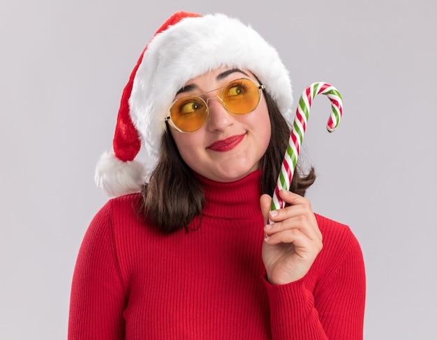 Junges mädchen im roten pullover und in der weihnachtsmannmütze, die die brille hält, die zuckerstange hält, die oben mit lächeln auf gesicht steht, das über weißem hintergrund steht