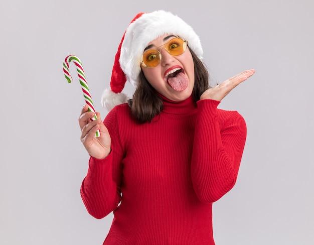 Junges mädchen im roten pullover und in der weihnachtsmannmütze, die gläser tragen, die glückliche und freche herausstehende zunge der zuckerstange halten, die über weißem hintergrund steht