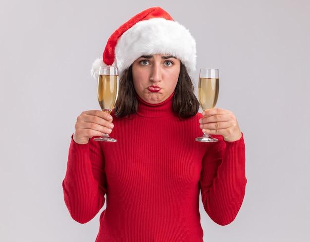 Junges mädchen im roten pullover und in der weihnachtsmannmütze, die zwei gläser champagner halten, betrachten kamera verwirrt und missfallen, die über weißem hintergrund stehen