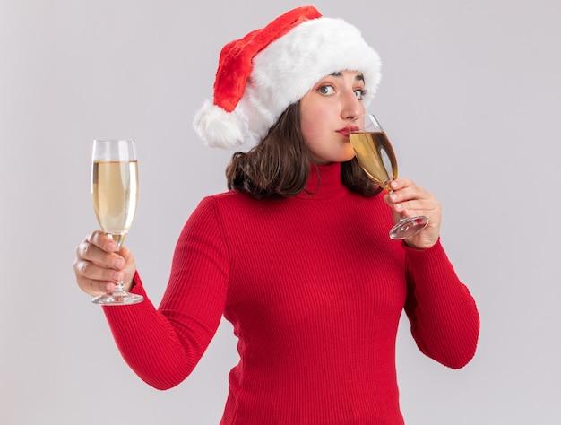 Junges mädchen im roten pullover und in der weihnachtsmannmütze, die zwei gläser champagner halten, die glückliches und positives stehen über weißem hintergrund trinken