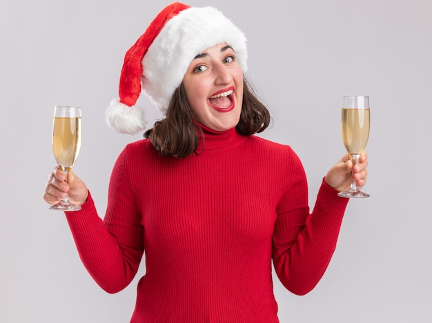 Junges mädchen im roten pullover und in der weihnachtsmannmütze, die zwei gläser champagner halten, die kamera glücklich und fröhlich lächelnd stehen über weißem hintergrund betrachten