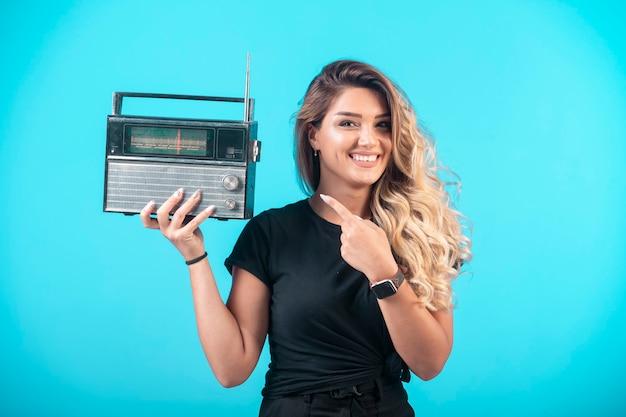 Junges mädchen im schwarzen hemd, das ein vintages radio hält und darauf zeigt.