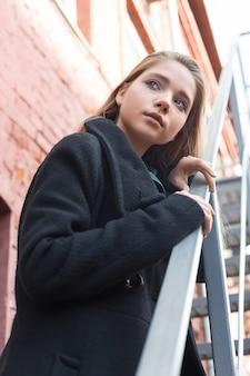 Junges mädchen im schwarzen mantel, der auf treppen mit backsteinmauer auf hintergrund steht. einsamkeit.