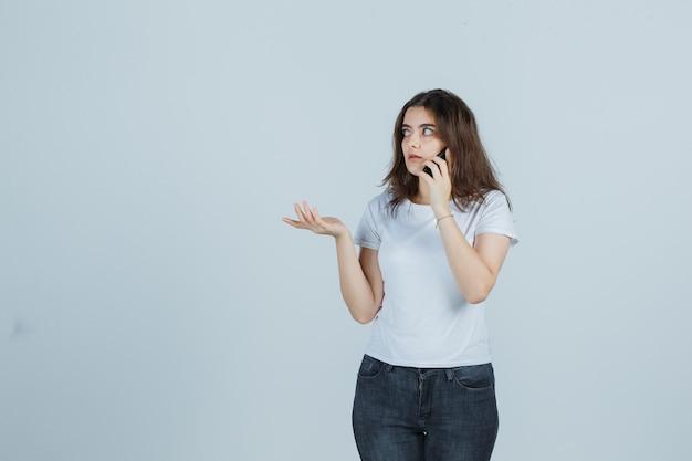 Junges mädchen im t-shirt, jeans, die auf handy sprechen, während sie so tun, als würden sie etwas zeigen und verwirrt aussehen, vorderansicht.
