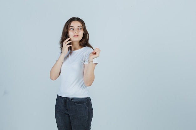 Junges mädchen im t-shirt, jeans, die auf handy sprechen, während wegschauen und ernst schauen, vorderansicht.