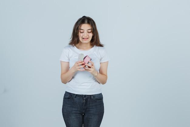 Junges mädchen im t-shirt, jeans, die geschenkbox öffnet, während sie hinein schaut und erstaunt schaut, vorderansicht.