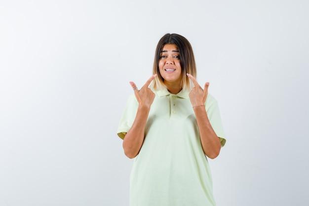 Junges mädchen im t-shirt zeigt auf zähne mit zeigefingern und schaut lustig, vorderansicht.